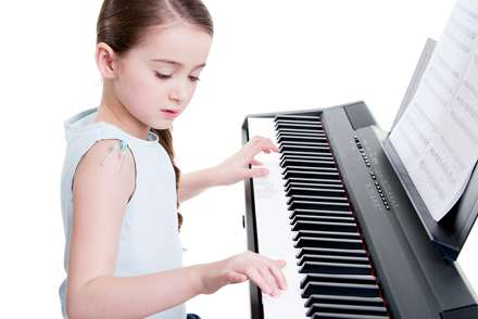 child practicing on the electric piano