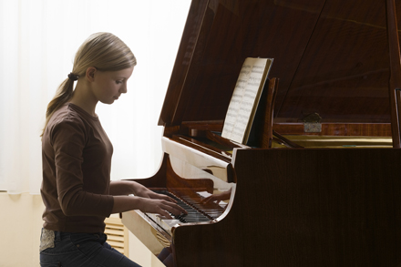 Teenage girl playing the piano with good posture